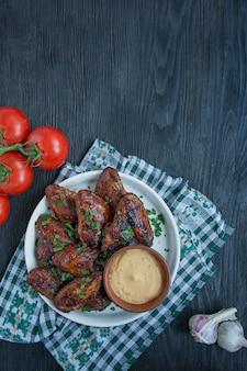 Gegrillte hühnerflügel mit soße und kräutern gebackene hühnerflügel in der wanne.