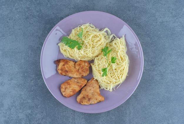 Gegrillte hühnerflügel und spaghetti auf lila teller.