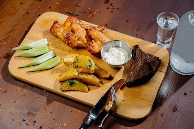 Gegrillte hühnerflügel vom grill schließen oben mit pommes frites, soße auf holzbrett auf einem dunklen tisch. fleischnahrungsmittelkonzept. gebratene hähnchenschenkel mit pommes frites