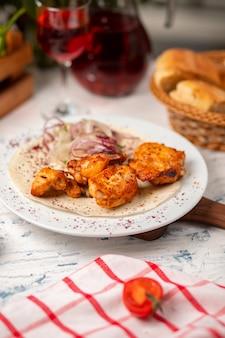 Gegrillte hühnernuggets, flügel, brust mit zwiebelsalat