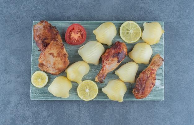 Gegrillte hühnerteile und salzkartoffeln auf holzbrett.