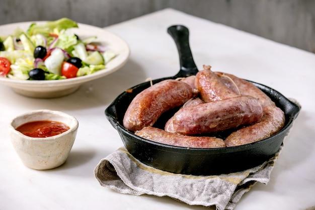 Gegrillte italienische würstchen salsiccia in gusseiserner pfanne, serviert mit tomatensauce und teller mit frischem gemüsesalat.