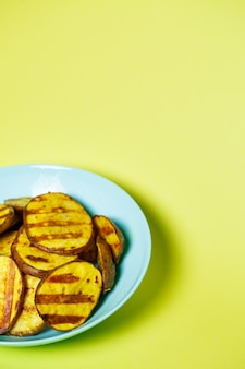 Gegrillte kartoffeln goldbraun in einem blauen teller auf gelbem grund
