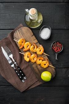 Gegrillte koriander-limetten-garnelen. garnelen am spieß mit knoblauchbuttersauce. set, auf schwarzem holztisch