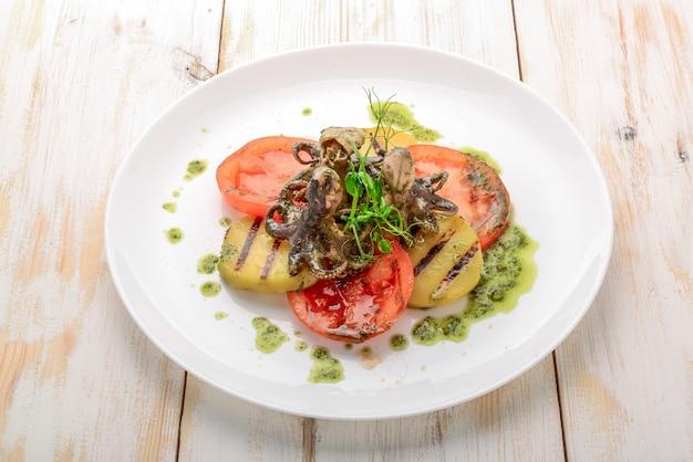 Gegrillte krake auf einer platte, gegrillte krake mit gegrilltem gemüse