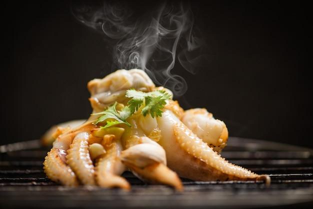 Gegrillte krake auf grillmeeresfrüchten bbq mit kräutern und gewürzen auf dunklem hintergrund