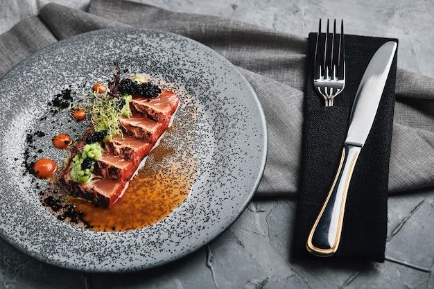 Gegrillte lachs-tagliata-draufsicht, schöne tischdekoration, schöne portion, traditionelles italienisches essen, grauer hintergrund, kopienraum. essen konzept.