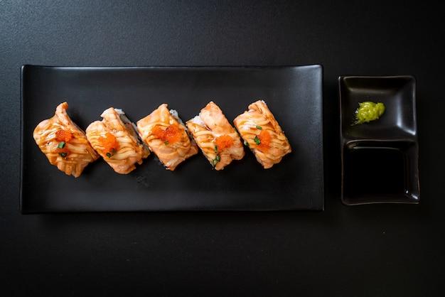 Gegrillte lachssushi-rolle mit sauce