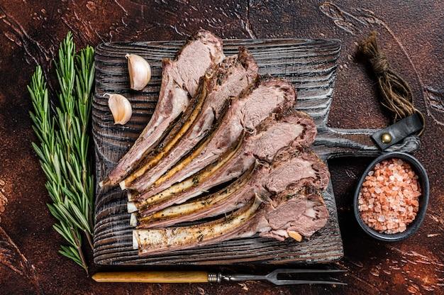 Gegrillte lamm hammel ribs chops steaks auf holzbrett. dunkler hintergrund. draufsicht.