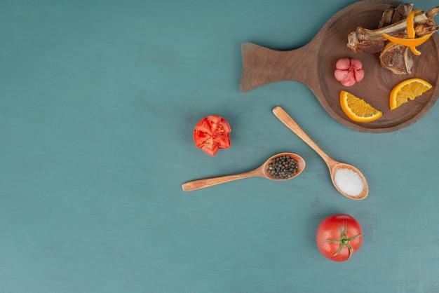 Gegrillte lammkoteletts mit gemüse auf blauer oberfläche
