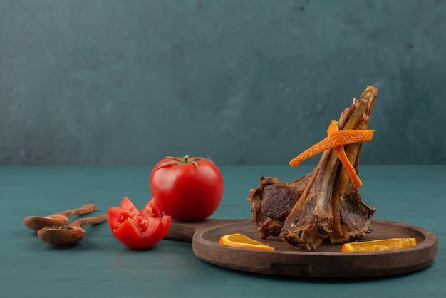 Gegrillte lammkoteletts mit geschnittenem gemüse auf blauem tisch.