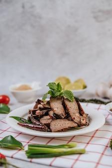 Gegrillte leberscheiben mit in scheiben geschnittenen limetten, karotten, chili, frühlingszwiebeln und minze.