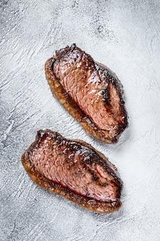 Gegrillte lendenstückkappe oder picanha-steak auf weiß. draufsicht.
