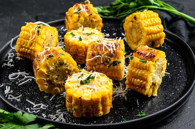 Gegrillte maiskolben mit petersilie und geriebenem parmesan bestreut.