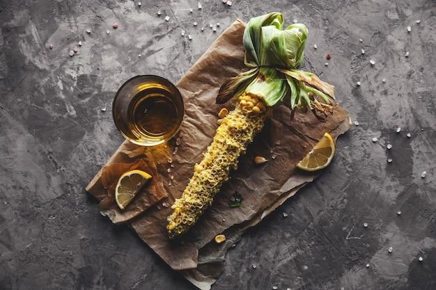 Gegrillte maiskolben mit sauce, koriande auf altem holzhintergrund. mexikanische nahrung. ansicht von oben. kopieren sie platz, gesundes essen, gemüse