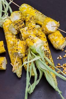 Gegrillte maisstücke und gegrillte maiskolben mit blättern. maiskörner. rostiger hintergrund.