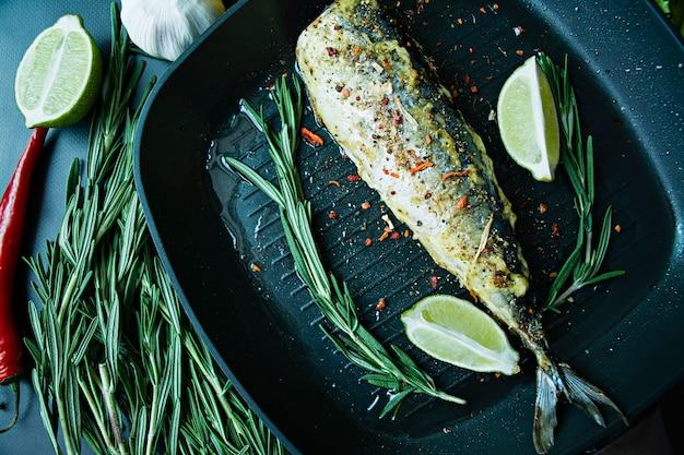 Gegrillte makrele in einer grillpfanne. richtige ernährung. dunkler hintergrund.