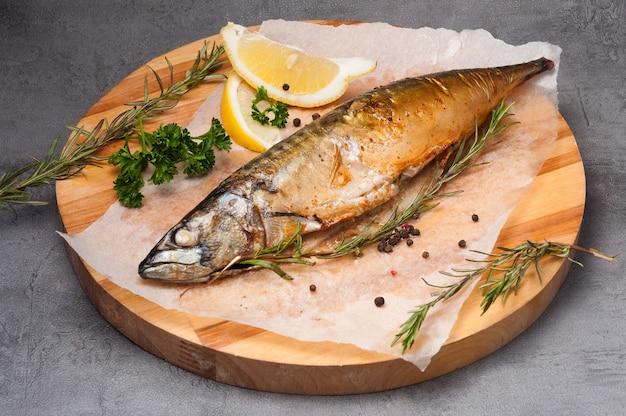 Gegrillte makrele mit zitrone und rosmarin auf einem holzbrett