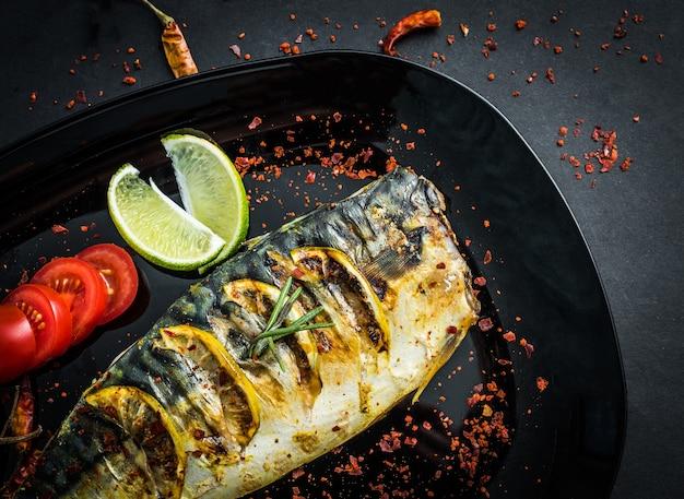 Gegrillte makrelenfilets auf schwarzem teller, gebratener fisch und gemüse
