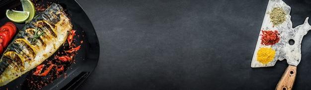 Gegrillte makrelenfilets mit limette auf schwarzem teller, draufsicht mit kopierraum