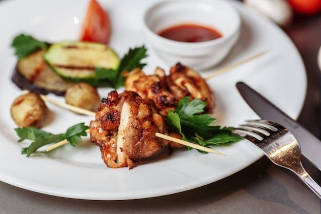 Gegrillte marinierte puten- oder hühnerfleisch-schaschlikspieße mit ketchup-sauce und gegrilltem gemüse auf rustikaler holztischoberfläche. traditionelles grillessen