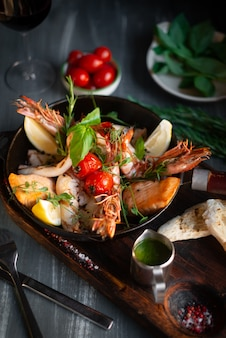 Gegrillte meeresfrüchte in einer pfanne auf einem holzbrett, garnelen, lachs, tintenfisch mit gewürzen und sauce