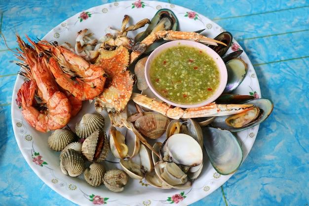 Gegrillte meeresfrüchte mit würziger sauce, grill mit krabben, garnelen, muscheln und tintenfischen mischen. lebensmittelkonzept.