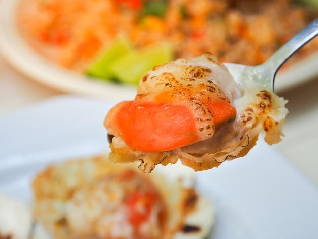 Gegrillte muschelschale mit butter und käse. thailändische meeresfrüchte gegrillte kamm-muscheln auf silbernem löffel.