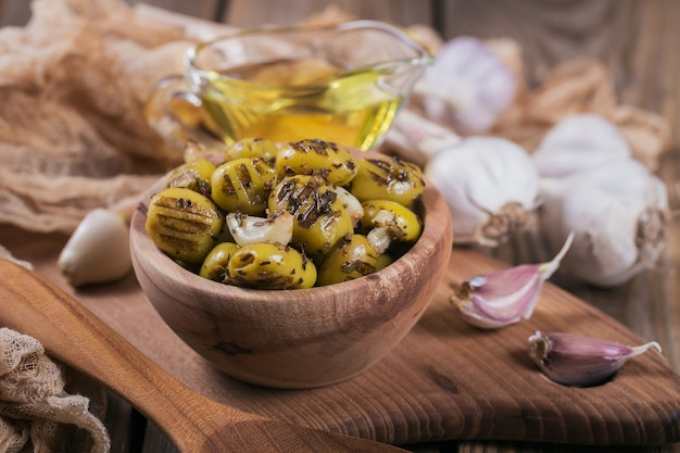 Gegrillte oliven mit knoblauch, olivenöl und gewürzen auf rustikalem holzhintergrund