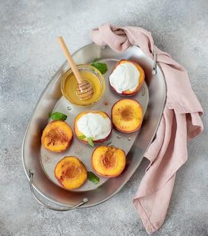 Gegrillte pfirsiche mit einer kugel eiscreme, honig