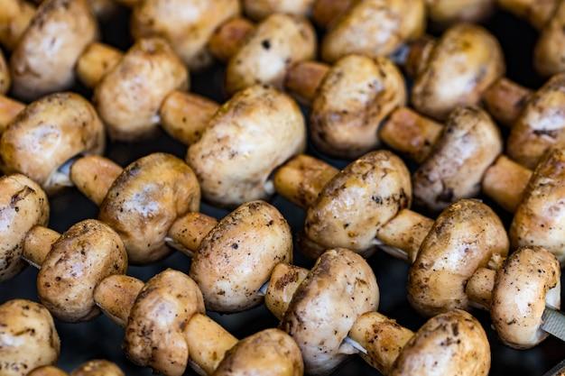 Gegrillte pilze am spieß in einem kohlenbecken gekocht, nahaufnahme.