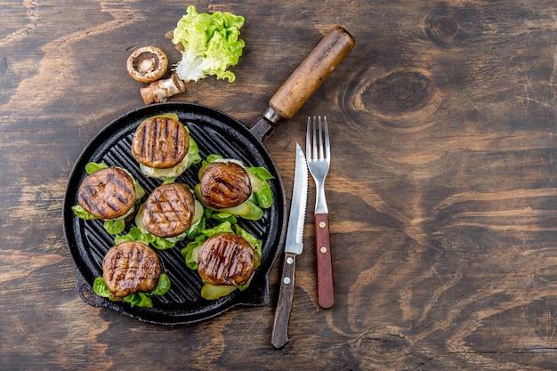 Gegrillte portobello brötchenpilzburger auf roheisengrillwanne ob hölzern, draufsicht