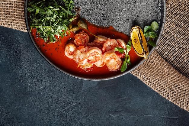 Gegrillte riesentigergarnelen mit tomatensauce und rucola, schöne portion vom küchenchef, grauer teller.