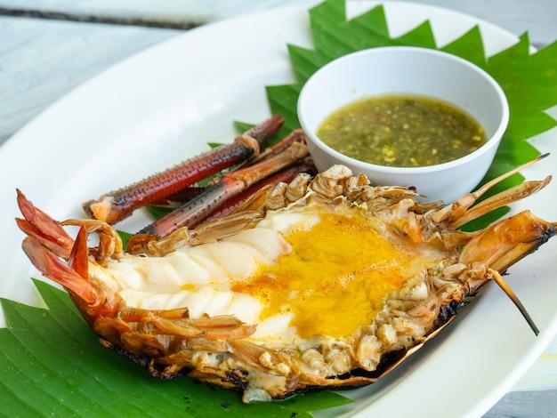 Gegrillte riesige flussgarnele mit würzigem meeresfrüchtedip auf platte, thailändisches lebensmittel kung pao.