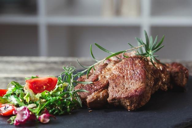 Gegrillte rindersteaks auf schwarzem steinschiefer. leckeres saftiges gegrilltes steak und salat mit tomaten. hauptgericht rindfleisch abendessen. abendessen mit steakbeef und salat. big-stake-fleisch auf schiefer.