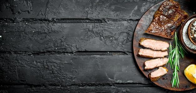 Gegrillte rindersteaks mit gewürzen und kräutern schwarz rustikal.