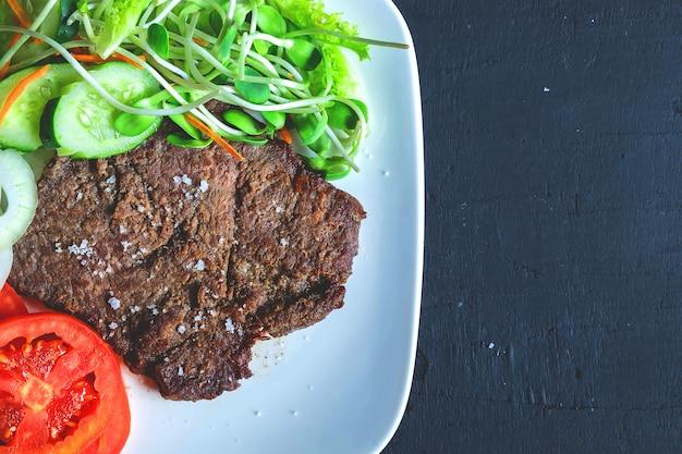 Gegrillte rindersteaks und gesunde salate auf dem tisch