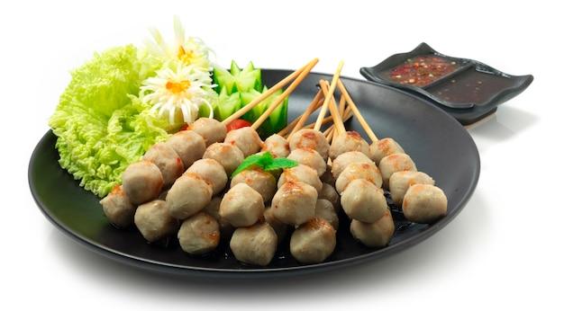 Gegrillte rindfleischbällchen mini-größe serviert sweet chili dipping sauce dekorieren geschnitzte gurken und gemüse seitenansicht