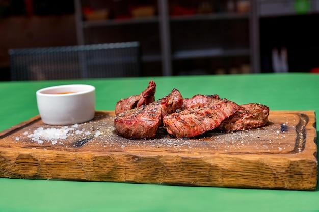 Gegrillte rindfleischmedaillons auf einem mit sauce garnierten küchenbrett aus holz