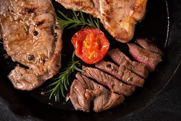Gegrillte rindfleischsteaks mit gewürzen auf schwarzer wanne
