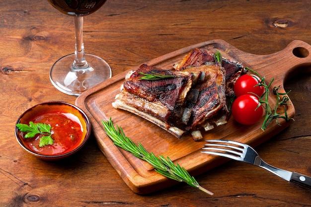 Gegrillte rippchen in barbecue-sauce und ein glas rotwein auf dem tisch