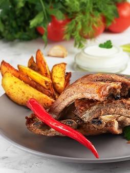 Gegrillte rippchen mit idaho-kartoffeln und gemüse auf dem teller. fettflecken auf fleisch. geringe schärfentiefe.