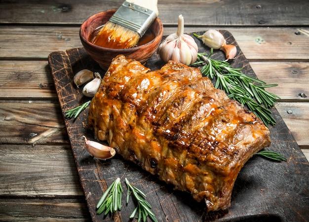 Gegrillte rippchen mit rosmarin, gewürzen und sauce auf einem rustikalen tisch.