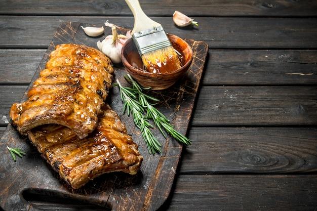 Gegrillte rippchen mit sauce, kräutern und gewürzen. auf einem hölzernen hintergrund.