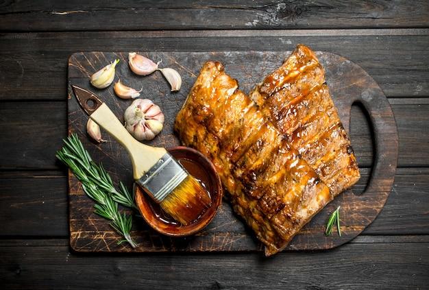 Gegrillte rippchen mit sauce, kräutern und gewürzen.