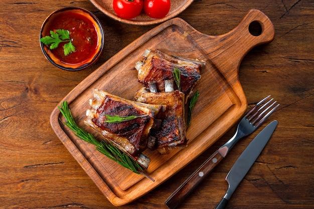 Gegrillte rippen in barbecue-sauce auf dem schneidebrett