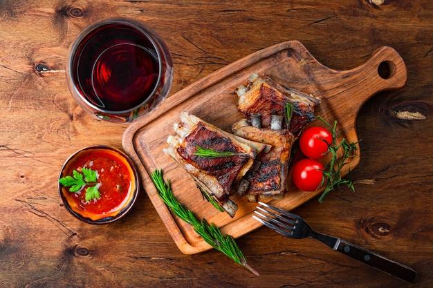 Gegrillte rippen in barbecue-sauce und ein glas rotwein draufsicht