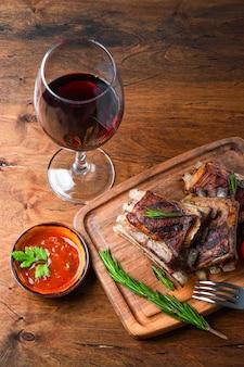 Gegrillte rippen in barbecue-soße und ein glas vertikales rotweinfoto