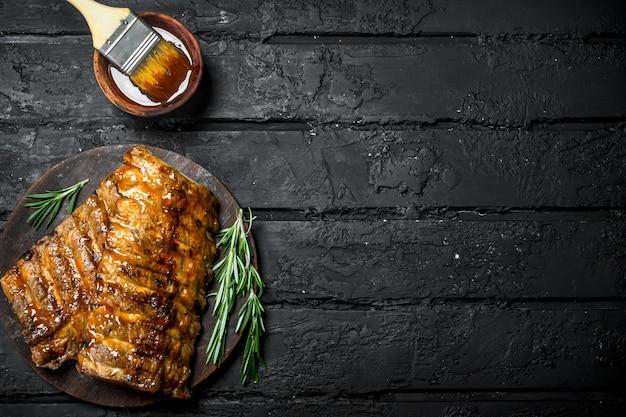 Gegrillte rippen mit sauce auf dunklem rustikalem tisch.