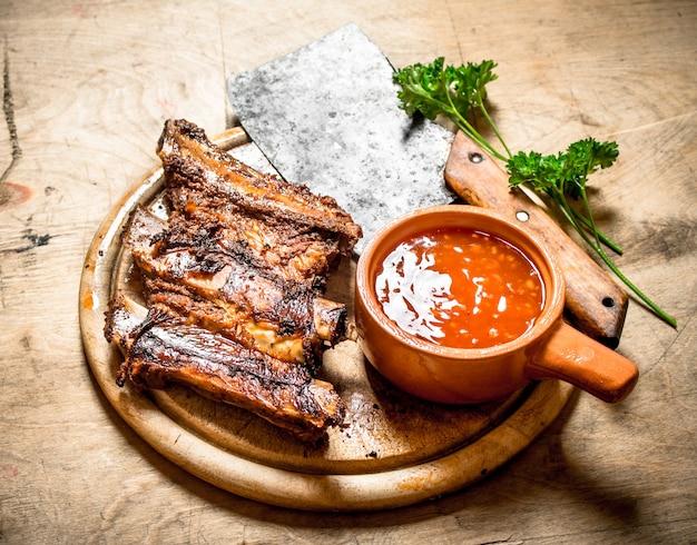 Gegrillte rippen mit tomatensauce und einem schnitzbeil auf hölzernem hintergrund